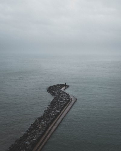 A minimal scene in which a stone pier reaches out into the sea. There is no line on the horizon where the sea and cloudy sky above meet.