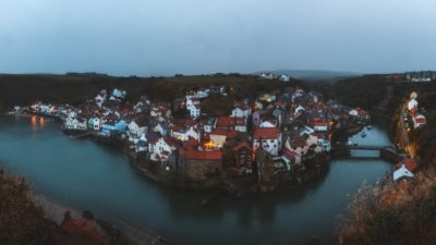 A quaint fishing town is enveloped by a man-made harbour that circulates the town. The weather is drab, wet and moody. The soft, warm glow of the streelights stands out against the dawn darkness.
