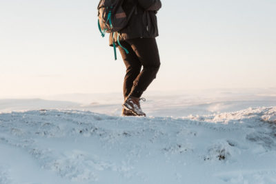 A commercial-style shot of walking boots caked in snow as a person walks along a snowy ridge.