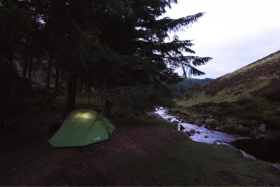 A small tent, illuminated by a light under the darkness of night, is pitched up next to a picturesque river