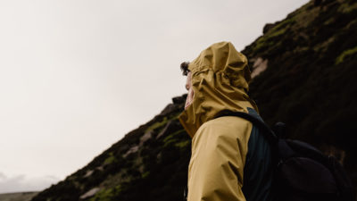A man in a yellow hood looks moodily out over the moorlands