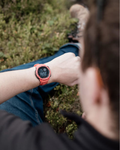 A photo over the shoulder of a person checking the time on their outdoor watch