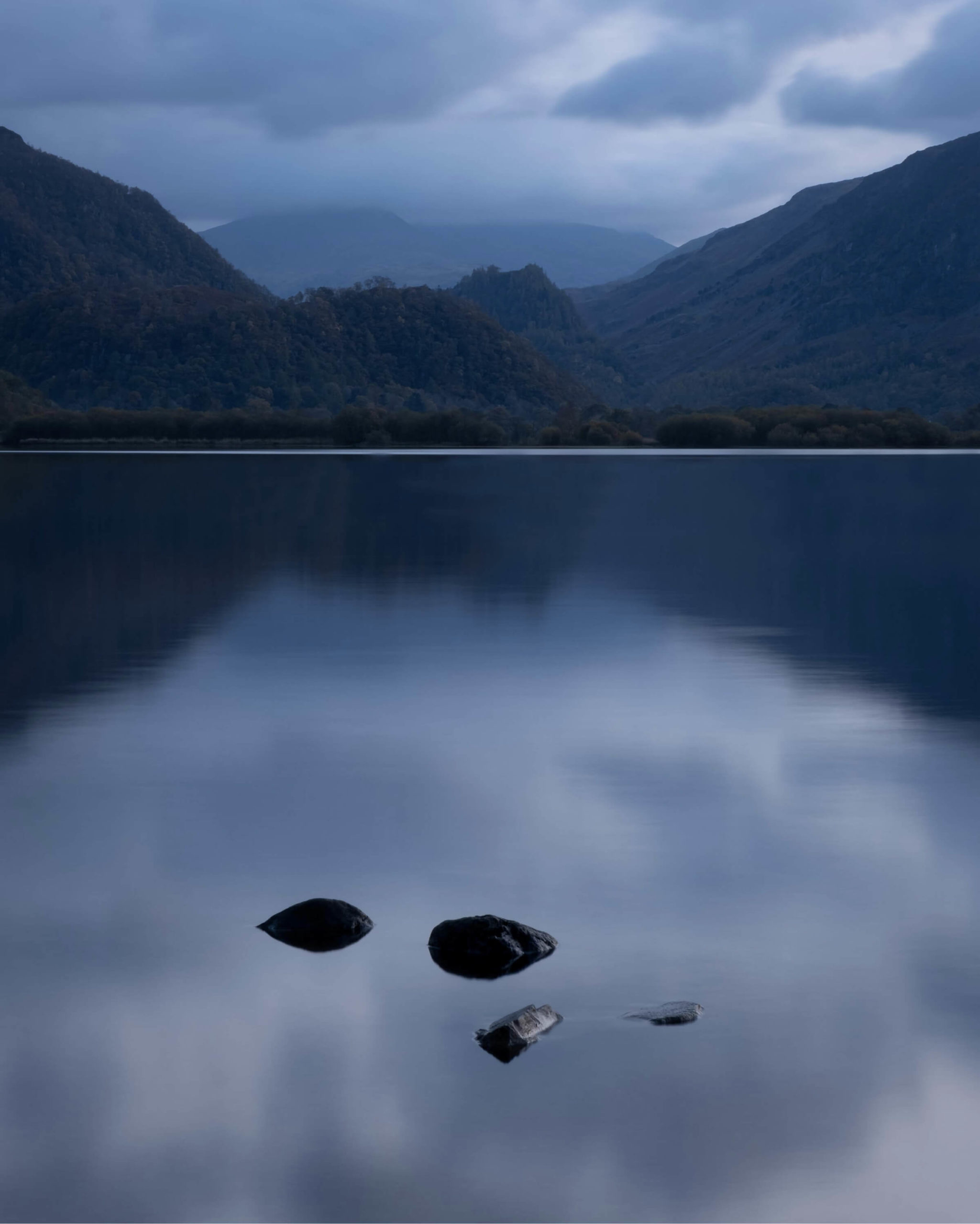 A small arrangement of four smooth stones sit in a still lake at blue hour. In the distance, mountains covered in trees are reflected in the water's surface.