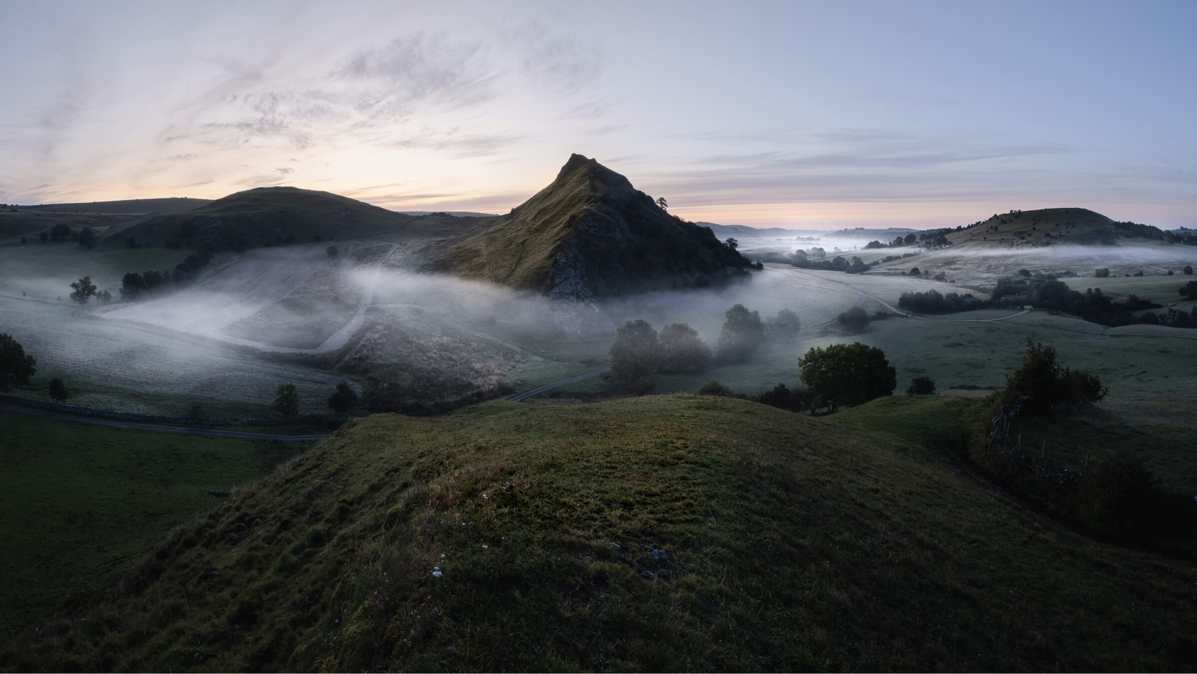 A sharp, jagged mountain juts out through a sprawling scene of farmers fields. A thin veil of mist hangs low in the valley and wraps itself around the mountain.