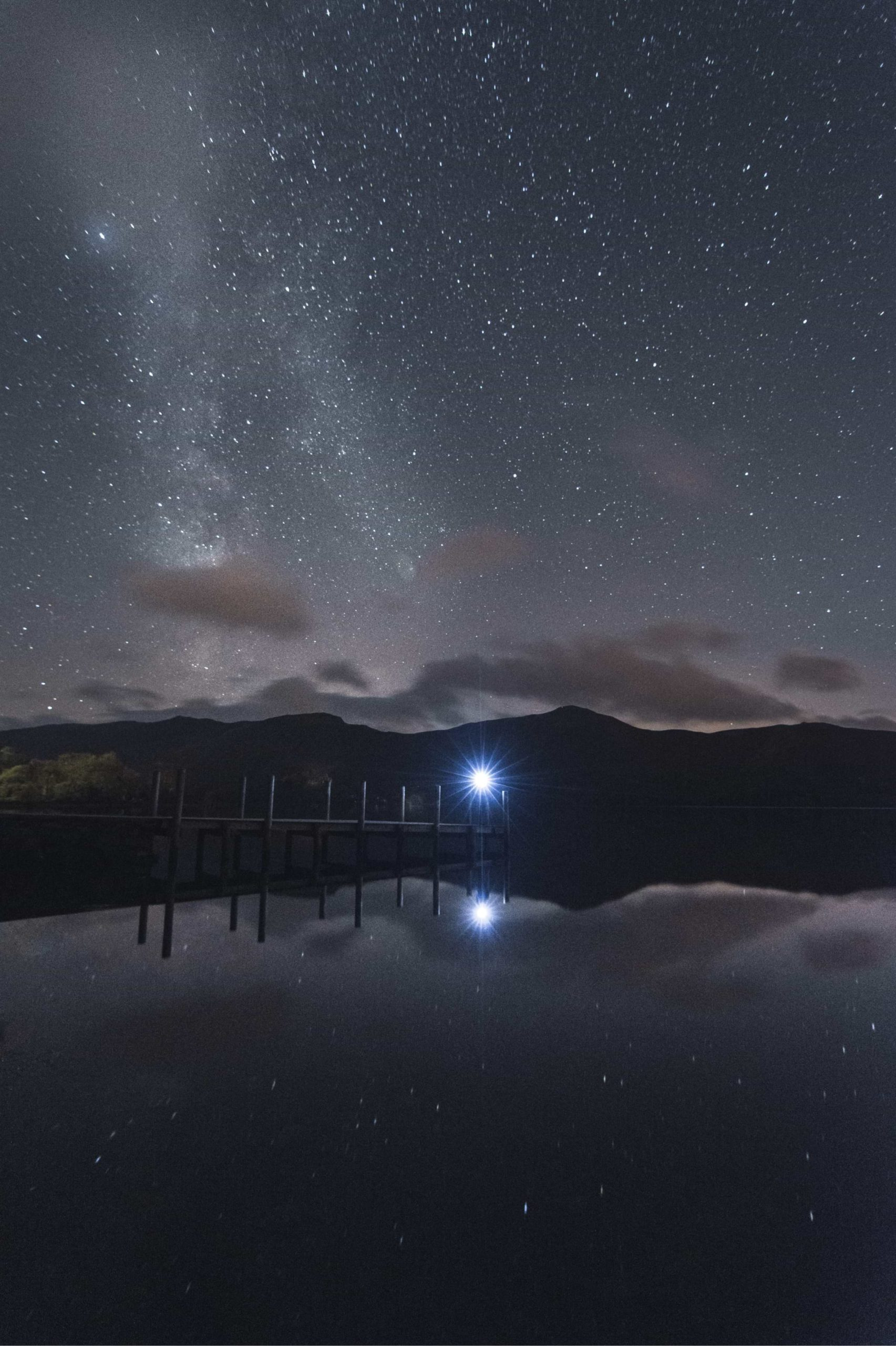 The milky way's galactic core can be seen striking down and meeting a jetty stuck out over the surface of a lake. At the end of the jetty, a person wearing a headtorch looks up to the starry sky.