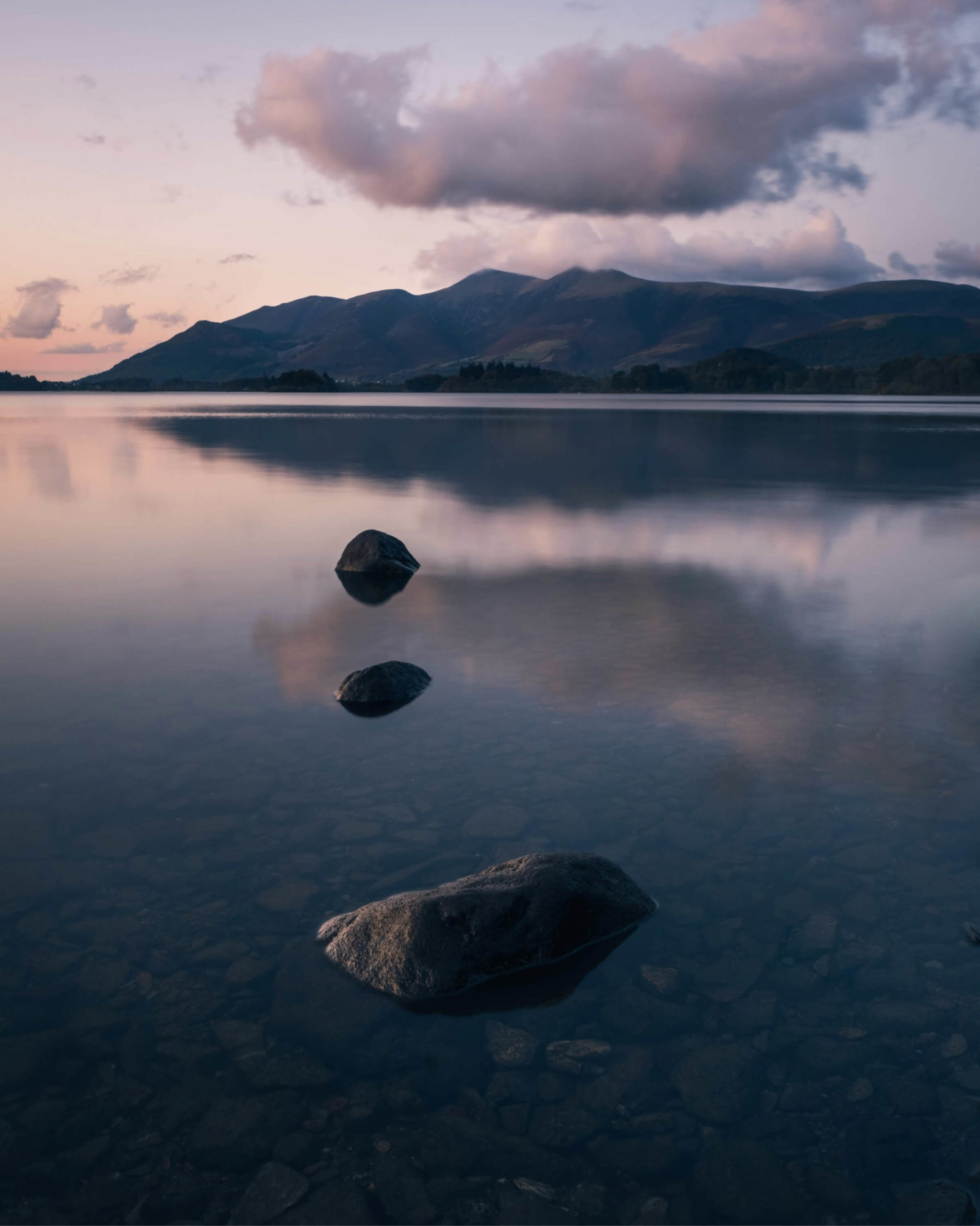 As the sun sets over a calm, still lake, pink fluffy clouds hover above a looming mountain range with three prominent peaks. An arrangement of three pebbles look like stepping stones on the water's surface.